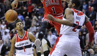 Chicago Bulls guard Derrick Rose (1) battles for the ball against Washington Wizards guard John Wall (2) as guard Nick Young looks on during the first half of an NBA game, Monday, Jan. 30, 2012, in Washington. (AP Photo/Nick Wass)