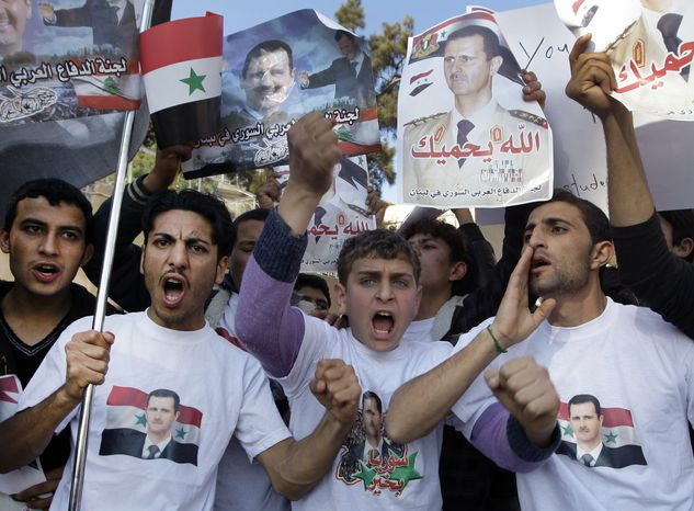 Protesters shout slogans as they carry pictures of Syrian President Bashar Assad and Syrian flags during a demonstration on Jan. 29, 2012, in front of the Russian Embassy in Beirut to express gratitude for the Russian position i