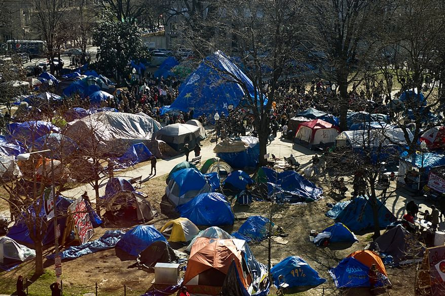 Occupy DC protesters cover the statue of Maj. Gen. James B. McPherson in the center of McPherson Square, top center, with a large blue tarp at noon on the day of a deadline the National Park Service set to remove camping material from McPherson Square and Freedom Plaza, Washington, DC, Monday, January 30, 2012. (Andrew Harnik / The Washington Times)