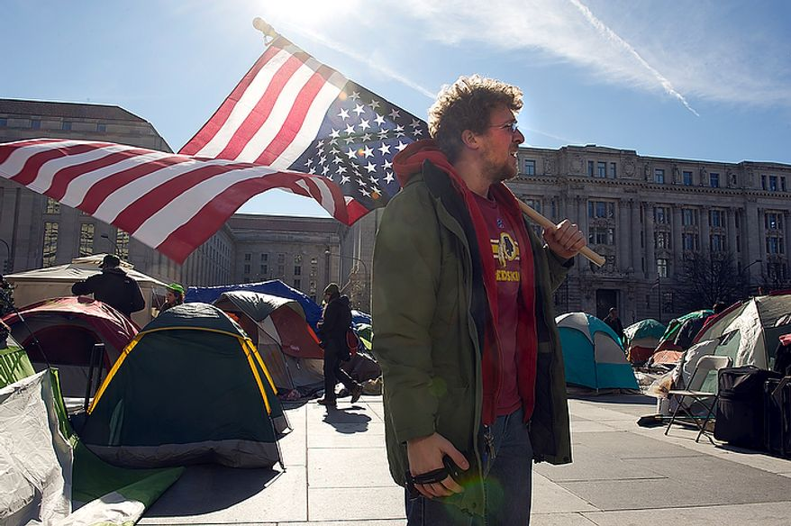 James McPherson of Norfolk, Va., stands with his upside-down American flag at the Freedom Plaza Occupy encampment in Washington, D.C. on Monday, Jan. 30, 2012, the day that Park Police said they would begin to enforce the no camping laws. In anticipation, Occupiers have cleaned out their tents and removed any sleeping bags and pillows. As of 1:30 p.m. no police had shown up. (Barbara L. Salisbury/The Washington Times)