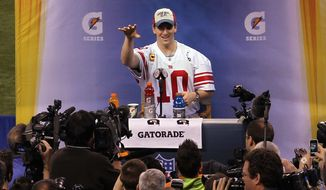 New York Giants quarterback Eli Manning throws a football during Media Day for NFL football's Super Bowl XLVI Tuesday, Jan. 31, 2012, in Indianapolis. (AP Photo/Paul Kazdan)