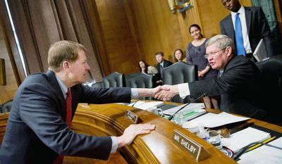 Richard Cordray, director of the Consumer Financial Protection Bureau (left), shakes hands with Sen. Tim Johnson, South Dakota Democrat and chairman of the Committee on Banking, Housing, and Urban Affairs, after a hearing on Capitol Hill on Tuesday. The committee held the hearing to review the first semiannual report of the Consumer Financial Protection Bureau. (Andrew Harnik/The Washington Times)