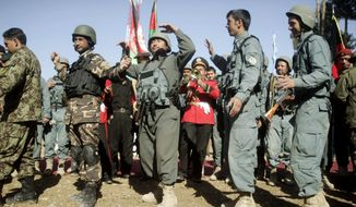 Afghan security forces celebrate Tuesday during a ceremony transferring authority from NATO-led troops to them in an area west of Kabul. The turnover to Afghan troops and police is to be finished by 2014. (Associated Press)