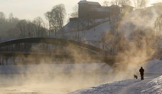 A man walks his dog near the Neris River in Vilnius, Lithuania, on Tuesday, Jan. 31, 2012, as morning temperatures plummeted to minus 9 degrees Fahrenheit. (AP Photo/Mindaugas Kulbis)