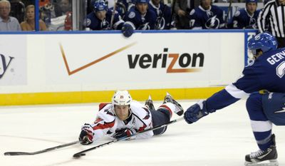 Washington Capitals center Brooks Laich, left, dives to slap the puck away from Tampa Bay Lightning defenseman Bruno Gervais during the first period of an NHL game in Tampa, Fla., Tuesday, Jan. 31, 2012. (AP Photo/Phelan M. Ebenhack)