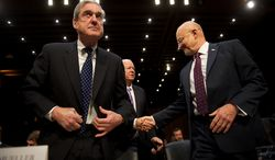 FBI Director Robert Mueller (left) and Director of National Intelligence James Clapper (right) are greeted by Sen. Saxby Chambliss, Georgia Republican and vice chairman of the U.S. Senate Select Committee on Intelligence, in the Hart Senate Office Building in D.C., before a hearing on worldwide threats. (Andrew Harnik/The Washington Times)