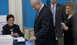 Israeli Prime Minister Benjamin Netanyahu (center), followed by his wife, Sara, casts his vote during the Likud party primary elections in Jerusalem on Tuesday, Jan. 31, 2012. (AP Photo/Bernat Armangue)