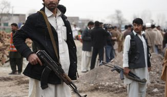 **FILE** Members of the lashkar, or local peace force, stand guard at the site of a suicide attack in Peshawar, Pakistan, on Jan. 30, 2012. A suicide bomber killed a leader of a militant group that has been fighting a rival outfit in northwest Pakistan close to the Afghan border, said police official Imtiaz Khan. (Associated Press)