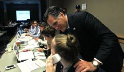 """Republican presidential candidate, former Massachusetts Gov. Mitt Romney, visits with campaign workers in his """"War Room"""" with advisers during the Florida primary election at the Tampa Convention Center in Tampa, Fla., Tuesday, Jan. 31, 2012. (AP Photo/Charles Dharapak)"""