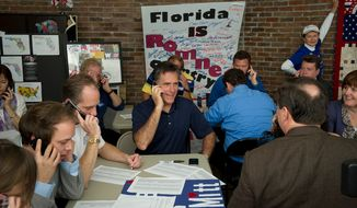Former Massachusetts Gov. Mitt Romney, surrounded by volunteers working the phones, makes calls to voters from his presidential campaign headquarters in Tampa, Fla., on Jan. 31, 2012. (Rod Lamkey Jr./The Washington Times)