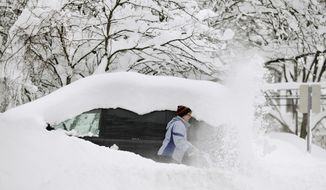 Chris Wolford digs out the driveway of her Fulton, N.Y., home on Jan. 30, 2012. More than 30 inches of snow fell in Fulton during the area's first lake-effect storm of the season. (Associated Press/The Post-Standard)