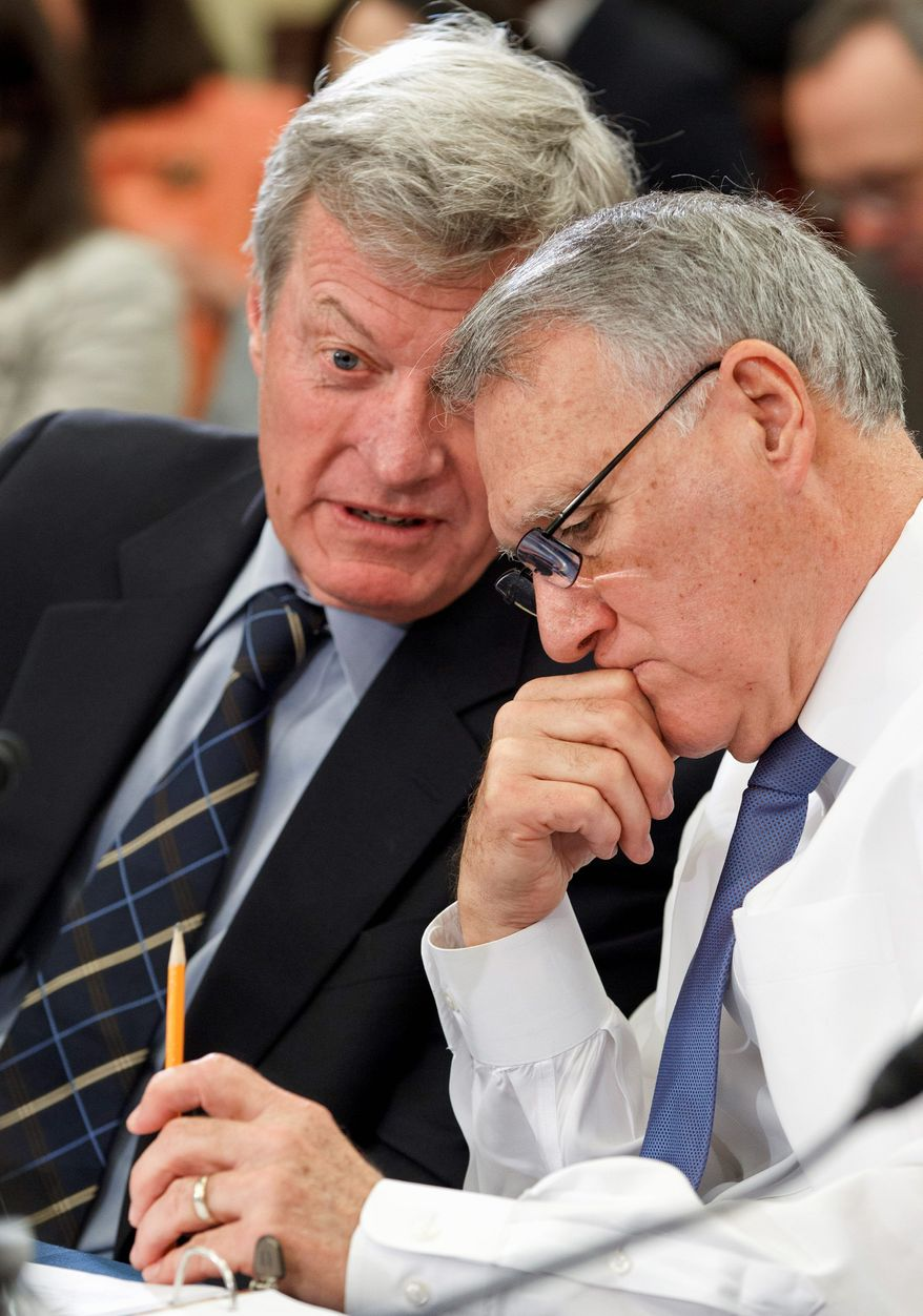 Senate Finance Committee Chairman Max Baucus, Montana Democrat (left), and Minority Whip Jon Kyl, Arizona Republican, confer during a meeting of the payroll-tax conferees Wednesday. Partisan debate on conditions to add to the federal unemployment benefits program threatens to bog down negotiations on extending the payroll-tax break. (Associated Press)