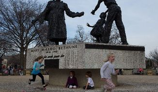 A 70-degree afternoon Wednesday gets people shedding jackets and enjoying the outdoors. As girls run past the statue of Mary McLeod Bethune in the District's Lincoln Park, 6-year-olds Amelia Huxley and Owen Stamper play underneath it. (Barbara L. Salisbury/The Washington Times)