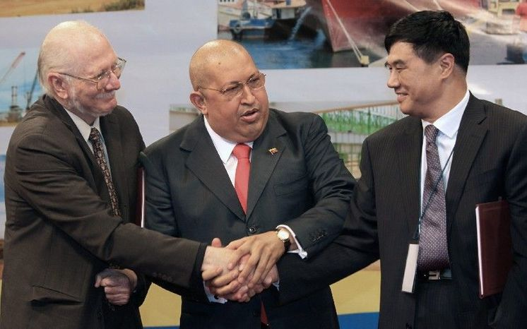 Celebrating at a November signing ceremony in Caracas, (from left) are Jorge Giordani, Venezuela's minister of planning and finance; President Hugo Chavez; and Zhan Xiaoquiang, China's vice minister of national development and re