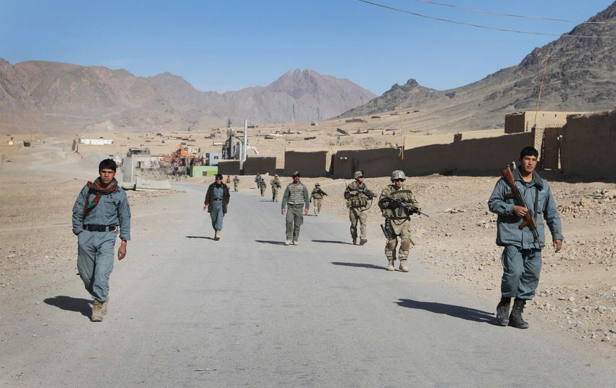 ** FILE ** Afghan policemen walk ahead of the U.S. soldiers with the NATO-led International Security Assistance Force (ISAF) during a foot patrol in Kandahar, south of Kabul, Afghanistan, in this Jan. 7, 2012, file photo. (AP Photo/Allauddin Khan, File)