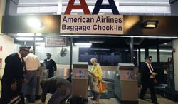 American Airlines baggage handlers help passengers check luggage at Dallas-Fort Worth International airport in Grapevine, Texas, on Feb. 1, 2012. (Associated Press)