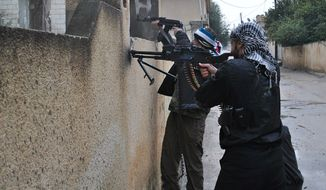 Syrian rebels take their position behind a wall as they fire their guns during a battle with Syrian government forces in the Rastan area of Homs province in central Syria on Tuesday, Jan. 31, 2012. (AP Photo)