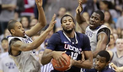 Georgetown's Greg Whittington, left, and Henry Sims, top right, defend Connecticut's Andre Drummon.  (AP Photo/Haraz Ghanbari)