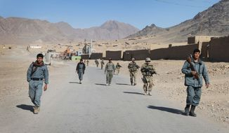 **FILE** Afghan policemen walk ahead of the U.S. soldiers with the NATO-led International Security Assistance Force (ISAF) during a foot patrol Jan. 7, 2012, in Kandahar, Afghanistan. (Associated Press)