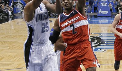Orlando Magic's Chris Duhon tries to get a shot off past Washington Wizards' John Wall during the first half Wednesday, Feb. 1, 2012, in Orlando, Fla. (AP Photo/John Raoux)
