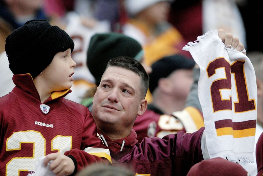 Fans react during a pre-game tribute to former Washington Redskin player Sean Taylor, who wore number 21, before against the Buffalo Bills at FedEx Field in Landover, Md., Sunday, December 2, 2007. Taylor was shot and killed in his Miami home last week. (Peter Lockley/The Washington Times)