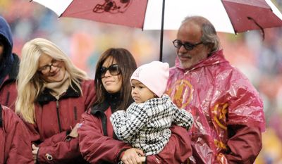 Sean Taylor's girlfriend, Jackie Garcia, holds their daughter, Jackie, during a pregame tribute to the slain Washington Redskins safety in November 2008. Taylor (right) was fatally shot the year before. (The Washington Times)