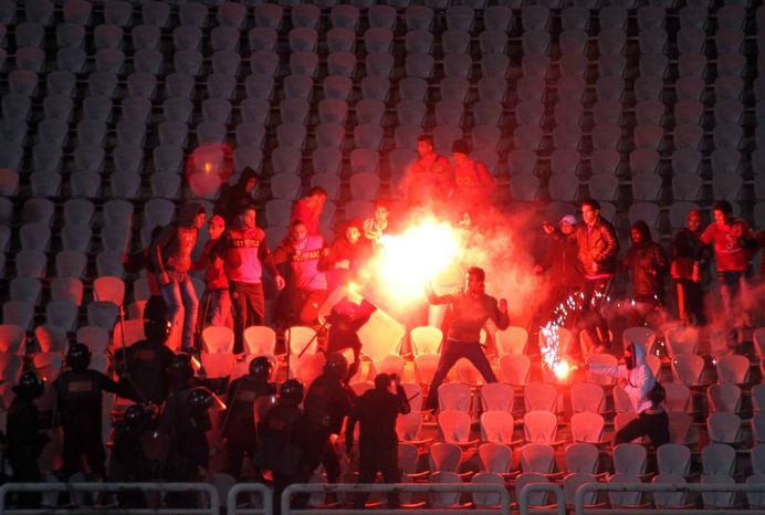 Soccer fans clash with riot police following a soccer match between the Al-Ahly and Al-Masry clubs at a stadium in Port Said, Egypt, on Wednesday, Feb. 1, 2012. (AP Photo)