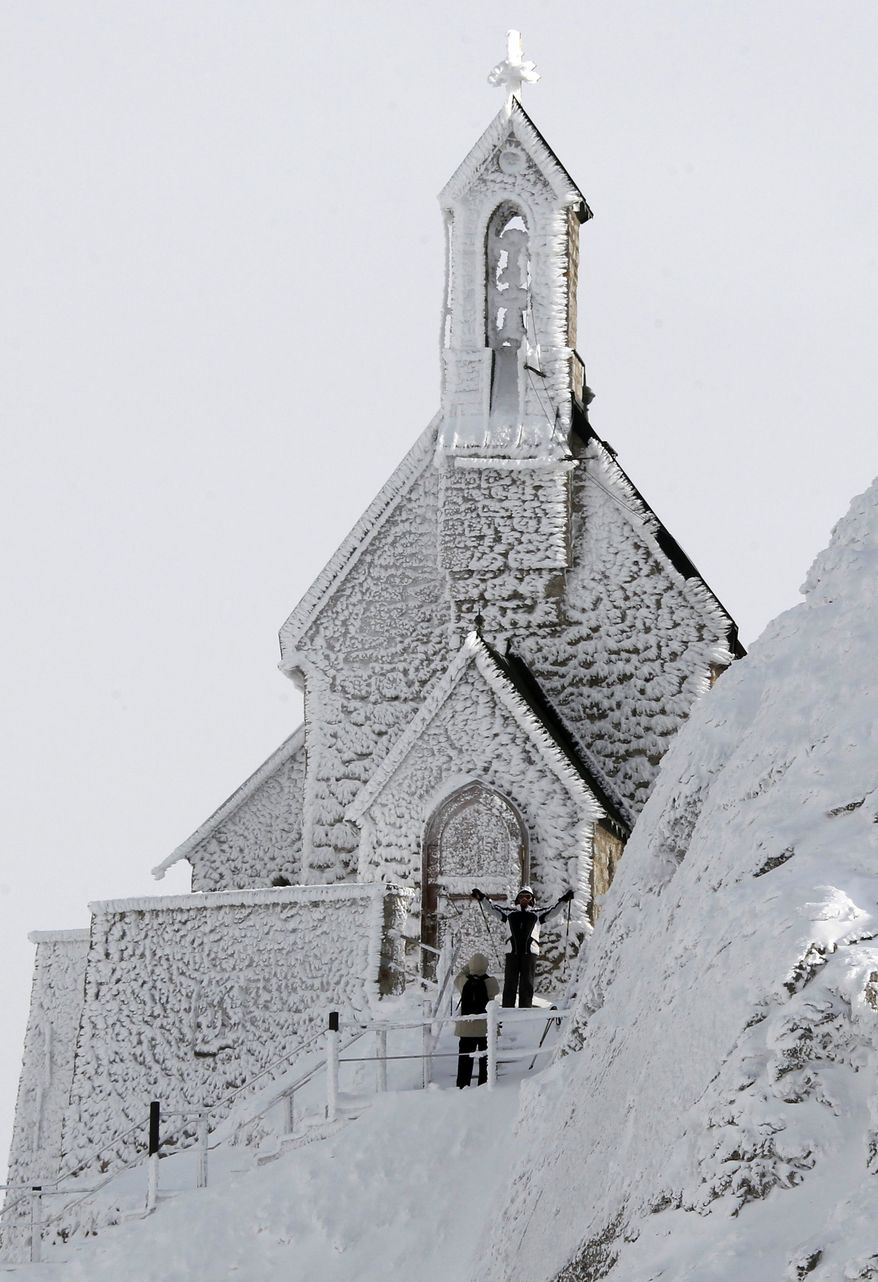 Hikers take pictures near the frost covered Wendelstein church, Germany's highest church, at 1838 meters (6030 feet) on the Wendelstein mountain near Bayrischzell, southern Germany, on Thursday, Feb. 2, 2012. A cold spell has reached central and eastern Europe with temperatures plummeting far below zero. (AP Photo/Matthias Schrader)