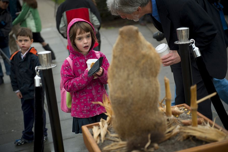 Ellen Lurie (center), 6, and her twin brother, Jonathan (left), join their father, Peter Lurie of Washington, at the inaugural Groundhog Day event at Dupont Circle in Washington on Thursday, Feb. 2, 2012. (Rod Lamkey Jr./The Washington Times)