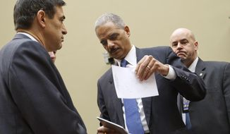 """Attorney General Eric H. Holder Jr. arrives on Capitol Hill in Washington on Thursday, Feb. 2, 2012, to testify before the House Oversight and Government Reform Committee hearing titled """"Fast & Furious: Management Failures at the Department of Justice."""" Rep. Darrell Issa, California Republican and committee chairman, is at left. (AP Photo/J. Scott Applewhite)"""
