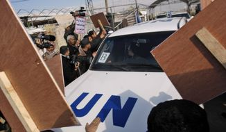 Palestinian demonstrators surround the convoy of U.N. Secretary-General Ban Ki-moon as it enters the Erez border crossing between Israel and Gaza on Thursday, Feb. 2, 2012. (AP Photo/Hatem Moussa)