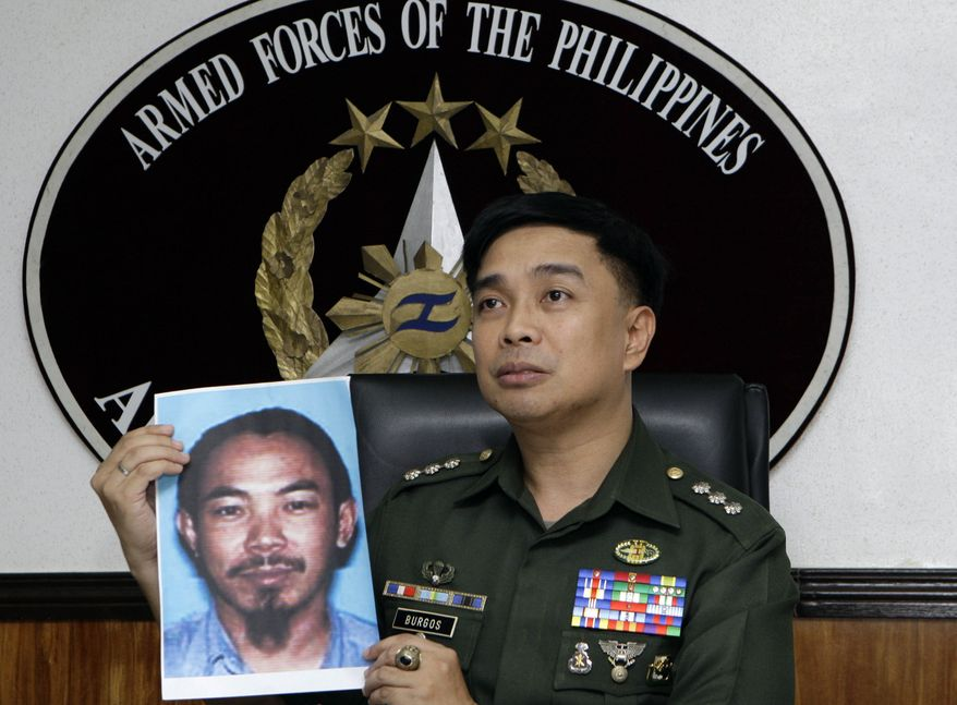 Col. Arnulfo Marcelo Burgos, a spokesman for the Philippine military, shows a picture of Malaysian Zulkipli bin Hir, also known as Marwan, a top leader of the regional, al-Qaeda-linked Jemaah Islamiyah terror network, during a press conference on Thursday, Feb. 2, 2012, in Quezon City, Philippines, north of Manila. (AP Photo/Pat Roque)