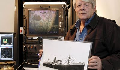 Greg Brooks, co-manager of Sub Sea Research, is seen aboard the salvage ship Sea Hunter in Boston Harbor Wednesday, Feb. 1, 2012, holding a picture of the British merchant ship Port Nicholson, which was sunk by a German U-boat in 1942 with a cargo of 71 tons of platinum now worth about $3 billion. (AP Photo/Winslow Townson)