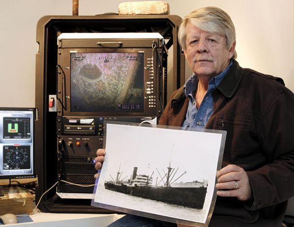 Greg Brooks, co-manager of Sub Sea Research, is seen aboard the salvage ship Sea Hunter in Boston Harbor Wednesday, Feb. 1, 2012, holding a picture of the British merchant ship Port Nicholson, which was sunk by a Ger
