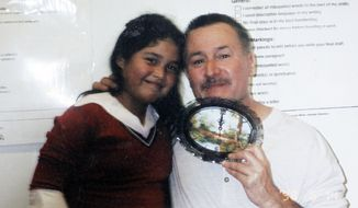 This 2003 photo provided by Flor Cervantes shows her sister, Angelica Zuniga, then a third-grader, with former Miramontes Elementary teacher Mark Berndt at the school in Los Angeles. Angelica Zuniga, 16, now a high school junior, said Berndt, who is suspected of taking bondage-style photographs of children in his class, never asked her or others to do anything strange or to play any inappropriate games. (Associated Press)