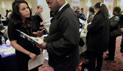 Daniela Silvero (left), an admissions officer at ASA College, discusses job opportunities Jan. 25, 2012, with Patrick Rosarie, who is seeking a job in IT, during JobEXPO's job fair, in New York. (Associated Press)