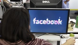 **FILE** This photo from Dec. 13, 2011, shows workers inside Facebook headquarters in Menlo Park, Calif. (Associated Press)