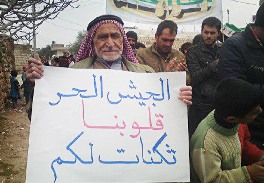 """In this citizen journalism image provided by the Local Coordination Committees in Syria and released Feb. 1, 2012, an anti-Syrian regime protester holds a poster in Arabic that reads, """"to the Syrian freedom soldiers, our hearts are bases for you,"""" as he walks during a demonstration in Idlib Province, north Syria. (Associated Press/Local Coordination Committees in Syria)"""