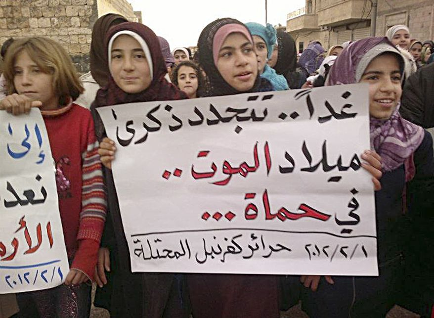 """In this citizen journalism image provide by the Local Coordination Committees in Syria and released Feb. 1, 2012, an anti-Syrian regime protester holds an Arabic poster that reads, """"tomorrow we shall remember a year's passing since the birth of death,"""" as she walks during a demonstration in Idlib Province, north Syria. (Associated Press/Local Coordination Committees in Syria)"""