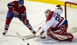 Washington Capitals goalie Tomas Vokoun makes a save off of Montreal Canadiens' Rene Bourque during second period NHL hockey action, Saturday, Feb. 4, 2012, in Montreal. (AP Photo/The Canadian Press, Paul Chiasson)