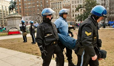 Park police officers arrest Occupy D.C. protester Dan Newell who refused to move away from a statue of Civil War Gen. James McPherson during an early morning raid on the Occupy encampment at McPherson Square, Washington, D.C., Saturday, Feb. 4, 2012. Police and protesters clashed throughout the day as tents and camping equipment were removed by park police and maintenance officials, some dressed in hazmat suits. (Andrew Harnik/The Washington Times)