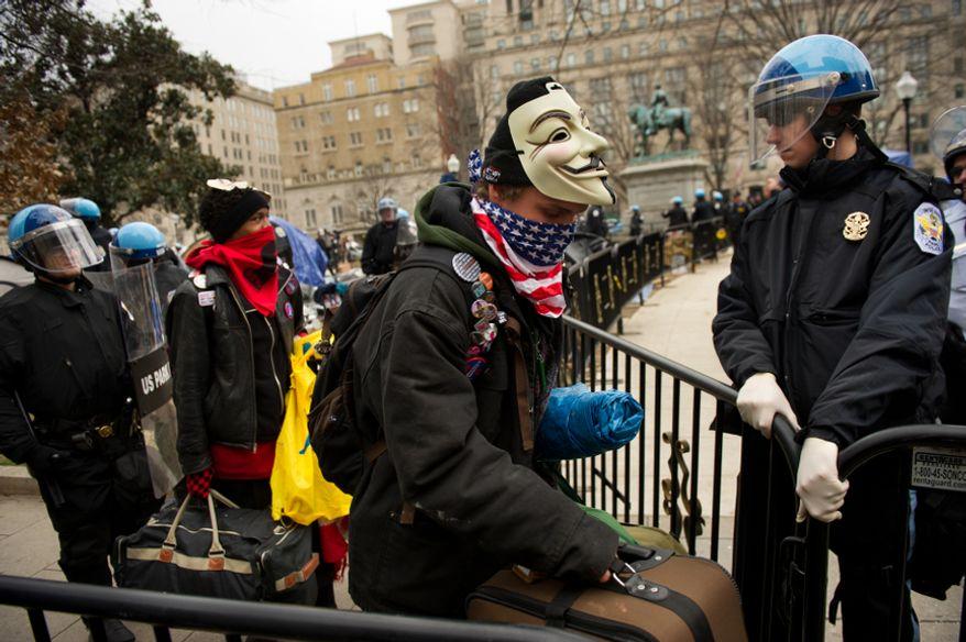 Protesters identifying themselves as Scout Fox of Charlotte, N.C., second from left, and Jake Roszak of Rochester, N.Y., center, are escorted out of a section of McPherson Square during a raid on the Occupy encampment, Washington, D.C., Saturday, Feb. 4, 2012. Police and protesters clashed throughout the day as tents and camping equipment were removed by park police and maintenance officials, some dressed in hazmat suits. (Andrew Harnik/The Washington Times)