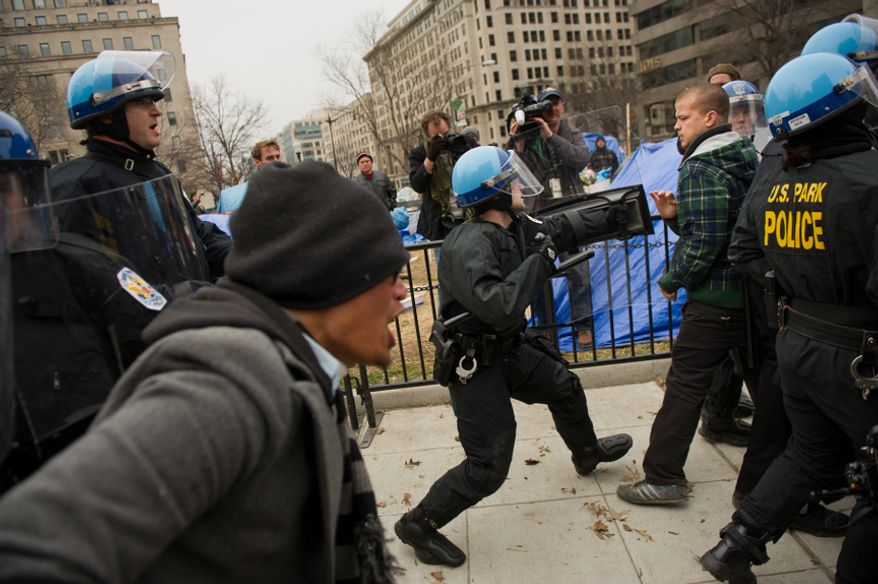 A raid on the Occupy encampment at McPherson Square turns ugly as Park Police officers try to clear protesters from sections of the park, Washington, D.C., Saturday, Feb. 4, 2012. Tents and camping equipment were removed by Park police and maintenance officials, some dressed in hazmat suits. (Andrew Harnik/The Washington Times)