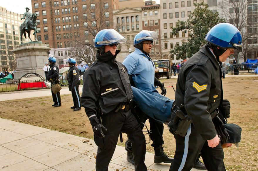 Park police officers arrest Occupy D.C. protester Dan Newell who refused to move away from a statue of Gen. James McPherson during an early morning, peaceful raid on the Occupy encampment at McPherson Square, Washington, D.C., Saturday, Feb. 4, 2012. Tents and camping equipment were removed by park police and maintenance officials, some dressed in hazmat suits. (Andrew Harnik/The Washington Times)