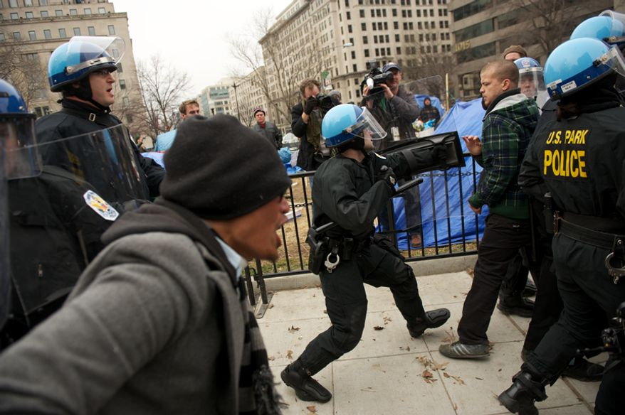 A raid on the Occupy encampment at McPherson Square in Washington, D.C., turns ugly as Park Police officers try to clear protesters from sections of the park, Saturday, Feb. 4, 2012. Tents and camping equipment were removed by park police and maintenance officials, some dressed in hazmat suits. (Andrew Harnik/The Washington Times)
