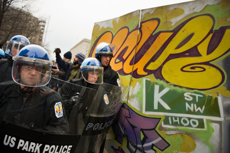 U.S. Park Police dressed in full riot gear hold back protesters during a raid on the Occupy encampment at McPherson Square, Washington, D.C., Saturday, Feb. 4, 2012. (Andrew Harnik/The Washington Times)