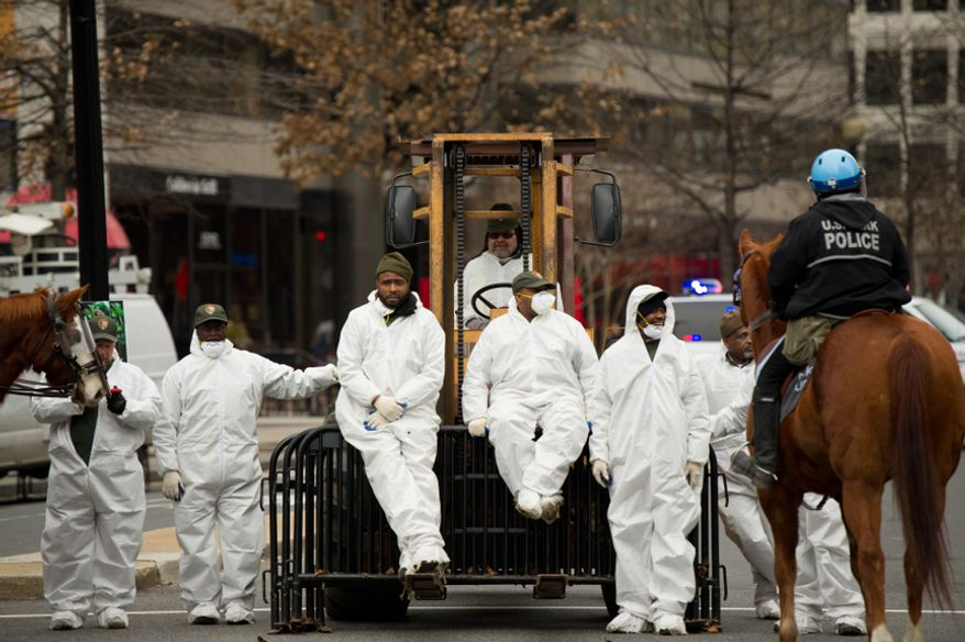 Park maintenance employees wait across K Street in hazmat suits for police to clear sections of the Occupy encampment in McPherson Square, Washington, D.C., Saturday, Feb. 4, 2012. (Andrew Harnik/The Washington Times)