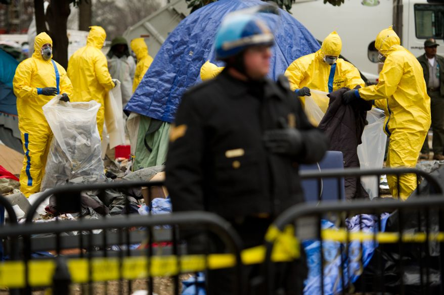 Tents and camping equipment are removed by park maintenance officials dressed in hazmat suits during a raid on the Occupy encampment in McPherson Square, Washington, D.C., Saturday, Feb. 4, 2012. Police and protesters clashed throughout the day as protesters were forced out of the square. (Andrew Harnik/The Washington Times)