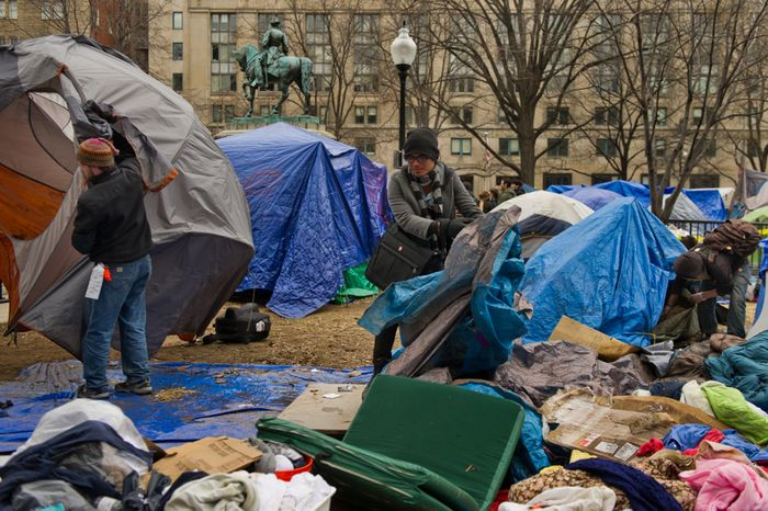 Michael Basillas of San Diego, Calif., center, and other protesters pack up their belongings during a raid on the Occupy encampment at McPherson Square, Washington, D.C., Saturday, Feb. 4, 2012. (Andrew Harnik/The
