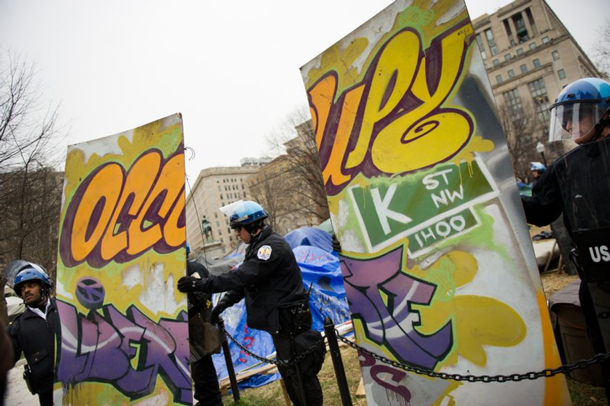 U.S. Park Police officers take apart an Occupy sign during a raid on the encampment at McPherson Square, Washington, D.C., Saturday, Feb. 4, 2012. Police and protesters clashed throughout the day as tents and camping equipment were removed by park police and maintenance officials, some dressed in hazmat suits. (Andrew Harnik/The Washington Times)